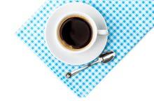 有茶碟和匙子碗筷的加奶咖啡杯子在蓝色方格的餐巾 库存图片