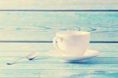 有茶碟和茶匙子的白色杯子在蓝色背景 免版税图库摄影