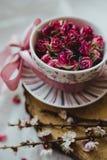 有茶碟的一个杯子用玫瑰和一把桃红色弓填装了 库存图片