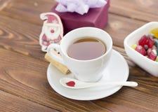 有茶碟的一个茶杯和匙子、一碗糖果,玩具圣诞老人和礼物盒 图库摄影