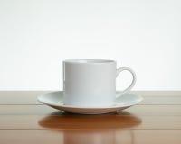 有茶碟的空的白色杯子在木头 库存照片
