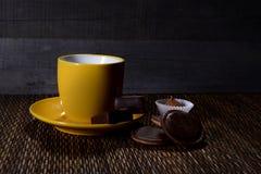 有茶碟的黄色杯在木背景 免版税图库摄影