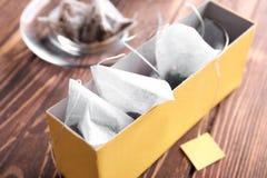 有茶袋的箱子在木桌上 库存照片