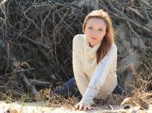 有草丛的年轻美丽的妇女在背景 库存照片