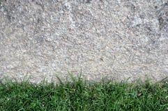 有草前景的花岗岩石墙 免版税库存图片