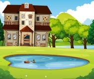 有草坪和池塘的老砖房子 皇族释放例证