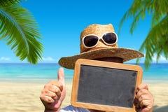 有草帽和太阳镜的人拿着空白石板黑板 库存图片