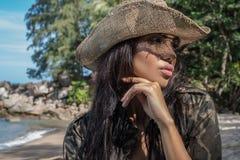 有草帽和太阳镜的美丽的深色的妇女在热带森林里 免版税库存图片