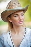 有草帽和白色女衬衫的可爱的白肤金发的女孩 免版税图库摄影