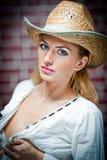 有草帽和白色女衬衫的可爱的白肤金发的女孩 免版税库存照片