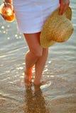 有草帽在手中和橙汁的妇女在海滩 免版税图库摄影