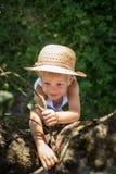有草帽尝试的攀登的逗人喜爱的男孩在树 库存图片