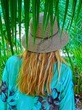 有草帽的一名妇女在与棕榈的后侧方 图库摄影