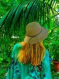 有草帽的一名妇女在与棕榈的后侧方 免版税库存图片