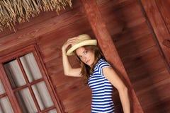 有草帽的白肤金发的夫人在夏时的木房子附近 免版税库存照片