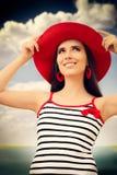 有草帽的美丽的女孩在蓝天 免版税库存照片