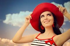 有草帽的美丽的女孩在蓝天 免版税图库摄影