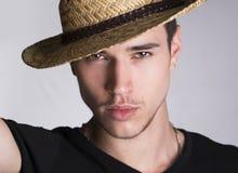 有草帽的英俊的闷热性感的年轻人 免版税库存照片