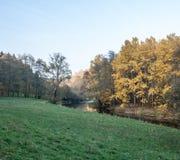 有草甸、五颜六色的秋天树和蓝天的Weisse Elster河在普劳恩附近 库存照片