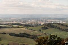 有草甸、领域和更小的小山的Pribor市在捷克共和国 免版税库存照片