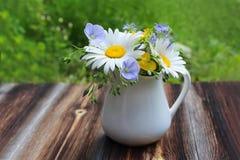 有草甸花束的白色水罐在木桌上开花 免版税库存照片
