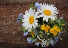 有草甸花束的白色水罐在木背景开花 免版税库存照片