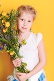 有草甸花的逗人喜爱的女婴 图库摄影