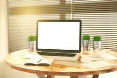 有草的空白的白色膝上型计算机屏幕在桶和日志 库存图片