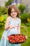 有草莓收获的可爱的小女孩 免版税库存图片