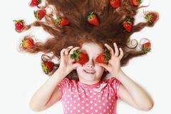 有草莓眼睛的美丽的小女孩 免版税库存照片