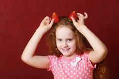 有草莓耳朵的滑稽的小女孩 库存照片
