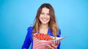 有草莓花束的一个逗人喜爱的少妇  影视素材