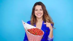 有草莓花束的一个逗人喜爱的少妇  股票录像