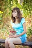 有荚莲属的植物篮子的女孩  库存图片
