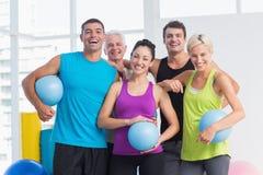 有药丸的快乐的人在健身演播室 库存照片