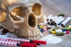 有药片、药物和注射器的头骨 免版税库存图片
