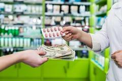 有药片和金钱的药剂师的和消费者的手 免版税库存照片