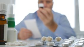 有药片在手中和一份医疗食谱的人 免版税库存图片
