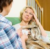 有药片的两名年迈的妇女在长沙发 免版税图库摄影