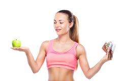 有药片的健身妇女在一只手上和绿色苹果在别的上 免版税库存图片