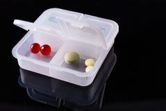 有药片的医疗箱子在黑背景 免版税库存图片