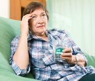 有药片的疲乏的女性领抚恤金者和杯水 库存照片