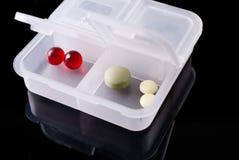 有药片的白色医疗容器在黑背景 反映 免版税库存照片