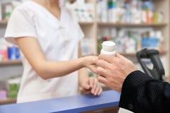 有药片的顾客买的白色瓶在药房 免版税库存照片
