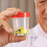 有药片的医生在容器 免版税库存图片