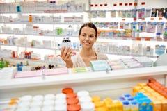 有药物瓶子的愉快的女性顾客在药房 免版税库存照片