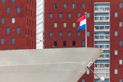 有荷兰旗子的经典船在现代大厦前面 免版税图库摄影