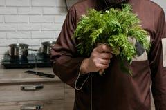 有荷兰芹和莳萝花束的厨师在厨房 图库摄影
