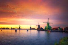 有荷兰风车和河的日落的,荷兰传统村庄 免版税库存图片