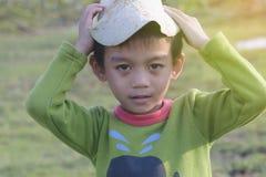 有莲花叶子的男孩在日落 库存图片